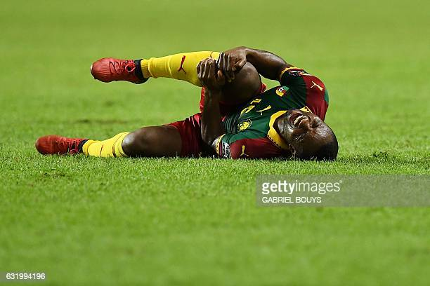 Cameroon's midfielder Sebastien Siani reacts in pain after falling during the 2017 Africa Cup of Nations group A football match between Cameroon and...