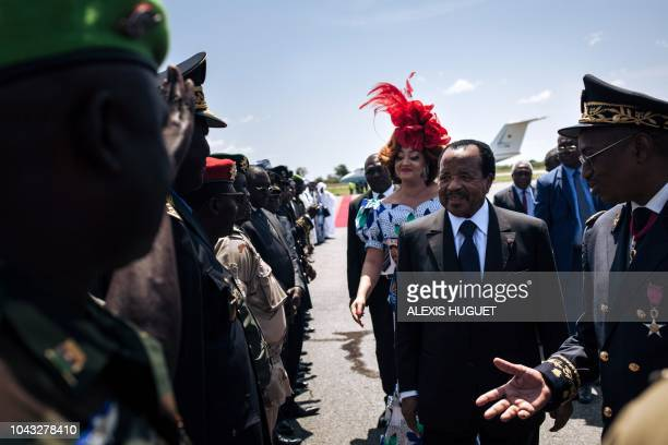Cameroon's President Paul Biya accompagnied by his wife Chantal Biya greets the military forces upon arrival at Maroua airport during his electoral...
