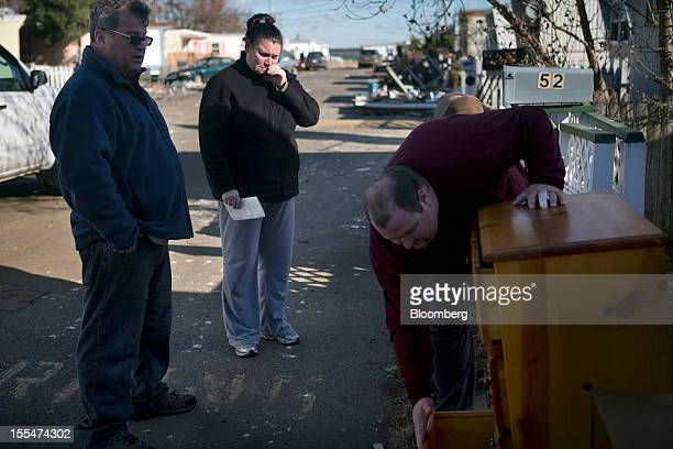 Cami Mazzarella cries while compiling a list of her belongings ruined during Hurricane Sandy for a FEMA claim as her fiance Daniel Parker left opens...
