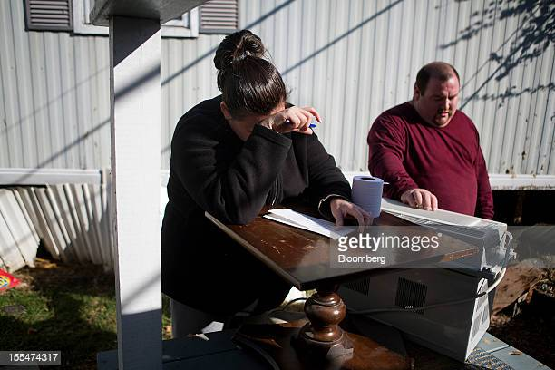 Cami Mazzarella left pauses while compiling a list of her ruined belongings for a FEMA claim as her fiance Daniel Parker looks on outside their home...