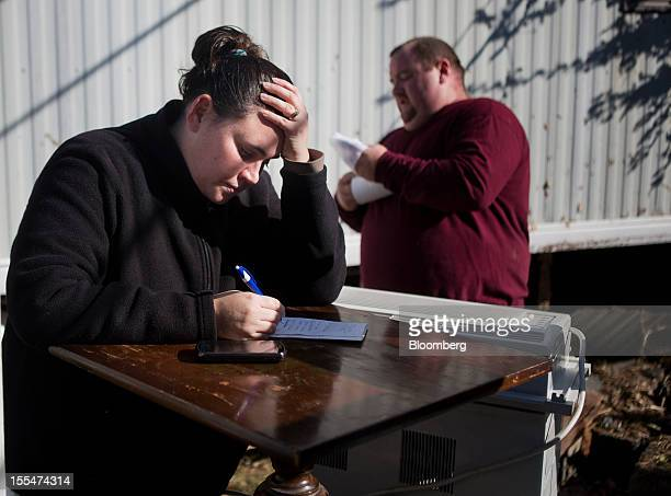 Cami Mazzarella pauses while compiling a list of her ruined belongings for a FEMA claim as her fiance Daniel Parker looks on outside their home in...