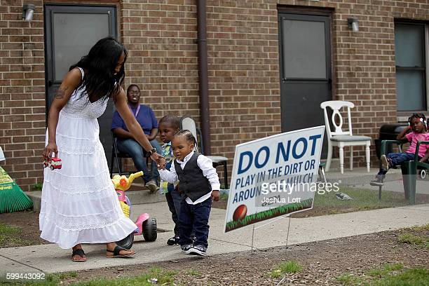 Camica Anderson left holds her son Logan Anderson's hand as other residents look on at the West Calumet Housing Complex on September 4 2016 in East...