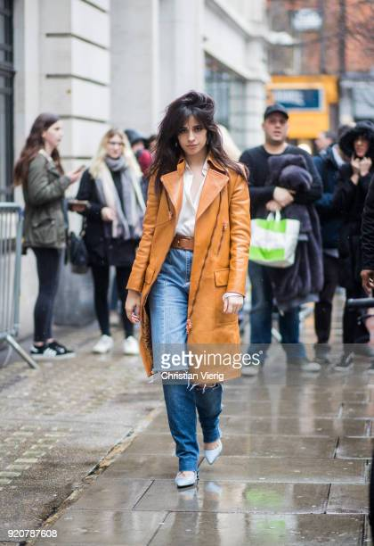 Camila Cabello wearing ripped denim jeans pointed shoes brown orange coat seen during London Fashion Week February 2018 on February 19 2018 in London...