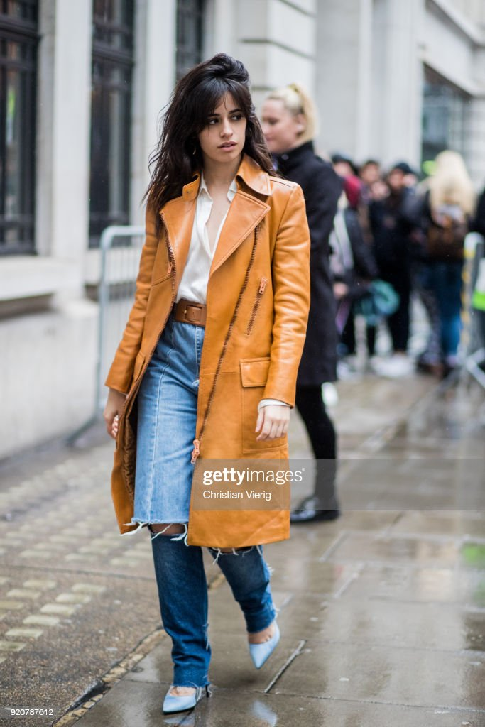 Camila Cabello wearing ripped denim jeans, pointed shoes, brown orange coat seen during London Fashion Week February 2018 on February 19, 2018 in London, England.