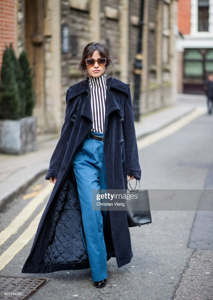 Camila Cabello wearing striped shirt Eloshi, blue pants Eloshi, boots Guiseppe Zanotti, sunglasses Tods, earrings Monse, navy coat Nina Ricci, bag seen during London Fashion Week February 2018 on February 20, 2018 in London, England.