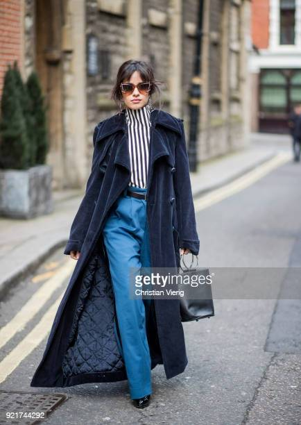 Camila Cabello wearing striped shirt Eloshi blue pants Eloshi boots Guiseppe Zanotti sunglasses Tods earrings Monse navy coat Nina Ricci bag seen...