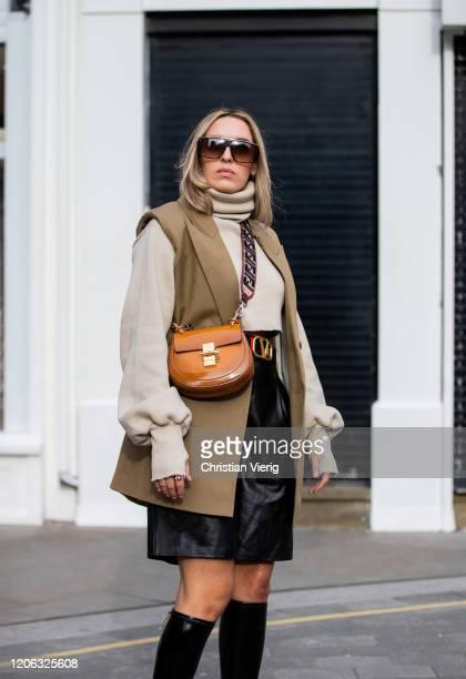 Camila Carril is seen wearing brown Fendi bag, Valentino belt, black leather pants, knit, brown vest outside 16Arlington during London Fashion Week...