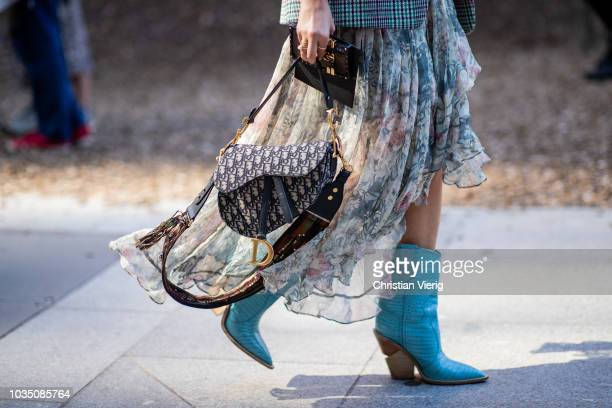 Camila Carril wearing checked blazer dress with floral print Dior saddle bag boots is seen outside Christopher Kane during London Fashion Week...
