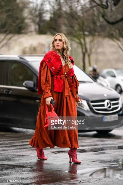 Camila Carril wears a red Fendi monogram wool pullover an orange dress red triangle shaped leather bag Fendi red pointy boots outside Ann...