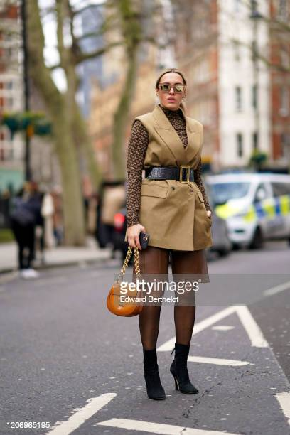 Camila Carril wears mirror sunglasses, a Burberry monogram brown turtleneck top, a sleeveless beige blazer jacket, a black leather large belt with...