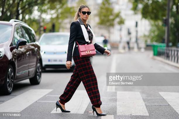 Camila Carril wears sunglasses, a black and white blazer jacket, a red bag, red and black checked print large pants, black high heeled shoes, outside...