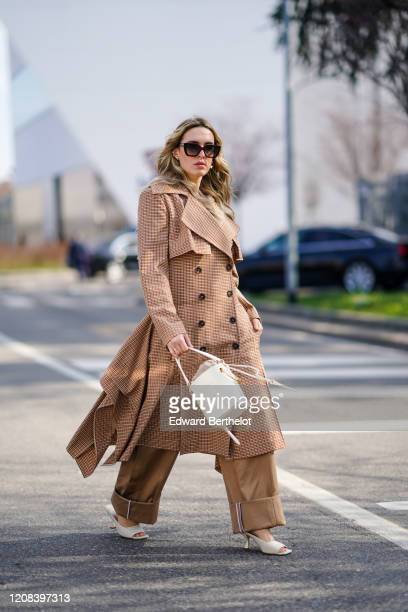 Camila Carril wears sunglasses a black top a long trench coat with printed checked patterns a Chloe bag brown pants white shoes outside BOSS during...
