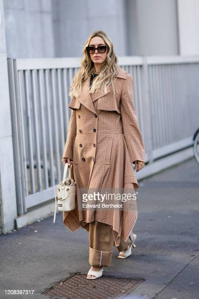 Camila Carril wears sunglasses, a black top, a long trench coat with printed checked patterns, a Chloe bag, brown pants, white shoes, outside BOSS,...