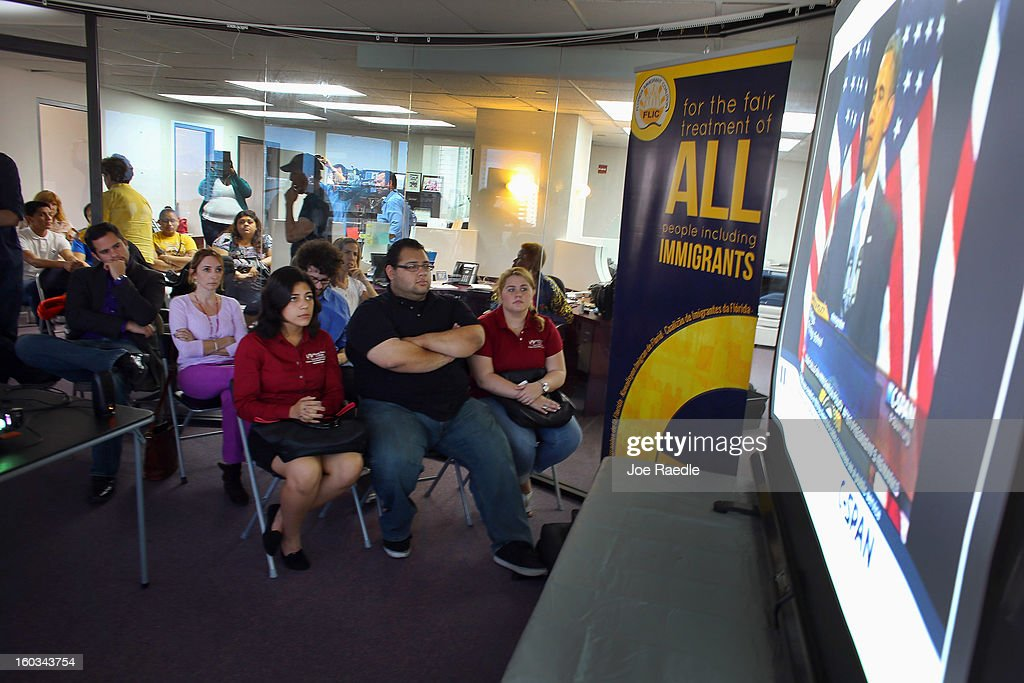 Camila Castellanos, Edwin Ramos and Zuleydi Baez (front row L-R) and other immigrant families and advocates watch on a projector screen as U.S. President Barack Obama makes remarks on immigration policy on January 29, 2013 in Miami, Florida. The President in his speech asked for a comprehensive overhaul of U.S. immigration laws.