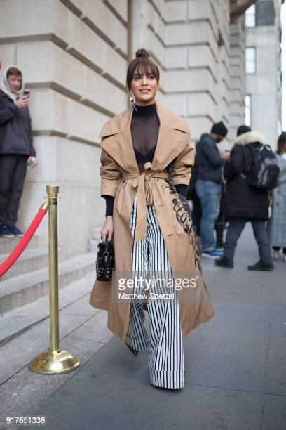 Camila Coelho is seen on the street attending OSCAR DE LA RENTA during New York Fashion Week wearing a tan with black design long coat with...