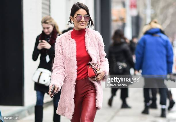 Camila Coelho is seen wearing a Cris Capoani pink fur coat with burgundy leather pants and red sweater at the Tibi show during New York Fashion Week...