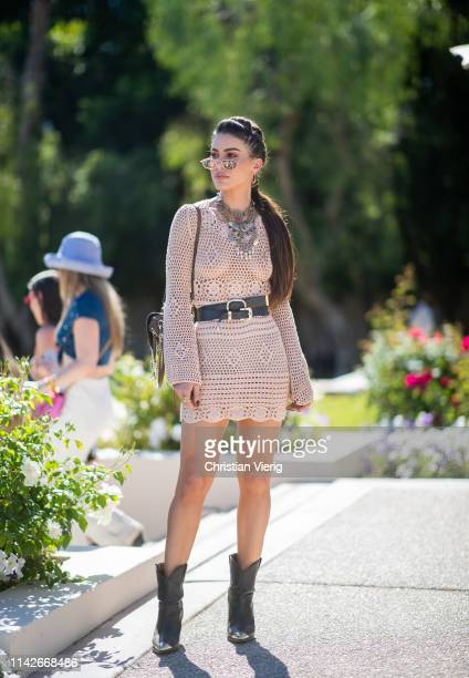 Camila Coelho is seen wearing beige sheer dress with belt and backpack at the Revolve Festival during Coachella Festival on April 13 2019 in La...