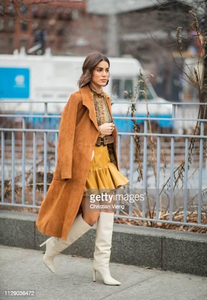 Camila Coelho is seen wearing brown coat, mustard mini skirt outside Zimmermann during New York Fashion Week Autumn Winter 2019 on February 11, 2019...