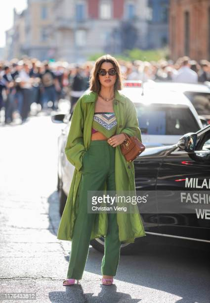 Camila Coelho is seen wearing green pants trench cropped top with print brown bag pink sandals outside the Ferragamo show during Milan Fashion Week...
