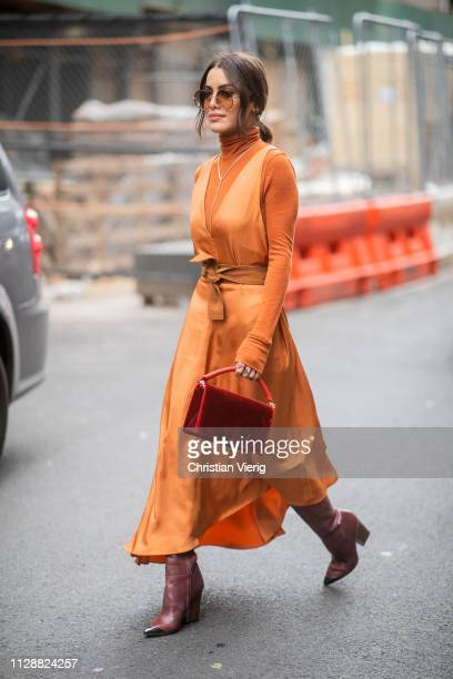 Camila Coelho is seen wearing orange turtleneck belted dress outside Tibi during New York Fashion Week Autumn Winter 2019 on February 10 2019 in New...