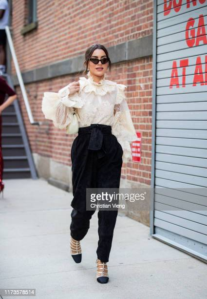 Camila Coelho is seen wearing ruffled blouse black high waist pants outside Zimmermann during New York Fashion Week September 2019 on September 09...