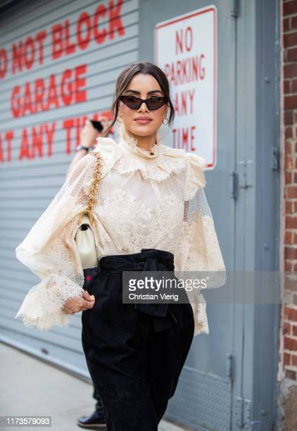 Camila Coelho is seen wearing ruffled blouse, black high waist pants outside Zimmermann during New York Fashion Week September 2019 on September 09,...