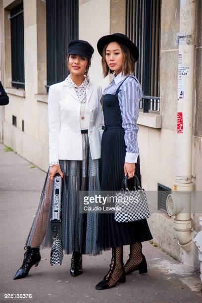 Camila Coelho wearing a black and white skirt a white jacket and black hat is seen with Aimee Song wearing a black hat a Dior black dress with a...