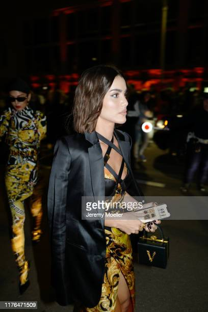 Camila Coelho wearing a complete Versace outfit and poses outside the Versace show during Milan Fashion Week Spring/Summer 2020 on September 20, 2019...