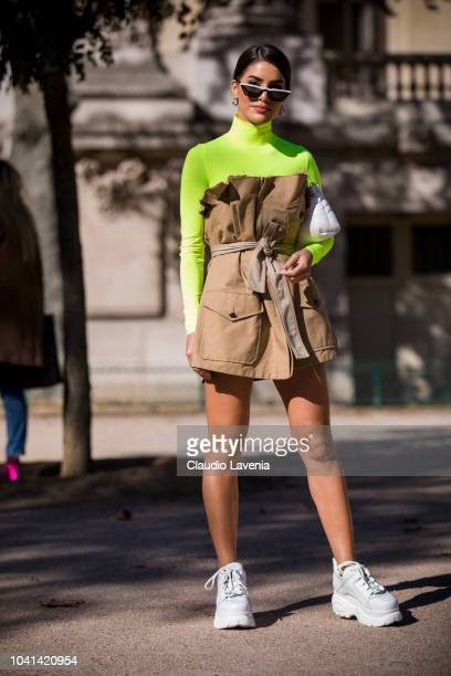 Camila Coelho wearing a neon green turtleneck beige dress and white sneakers is seen after the Maison Margiela show on September 26 2018 in Paris...