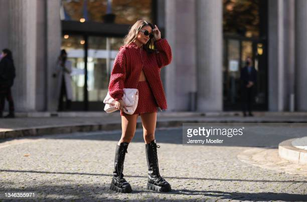 Camila Coelho wearing a red jacket and skirt with black boots outside Miu Miu Show on October 05, 2021 in Paris, France.