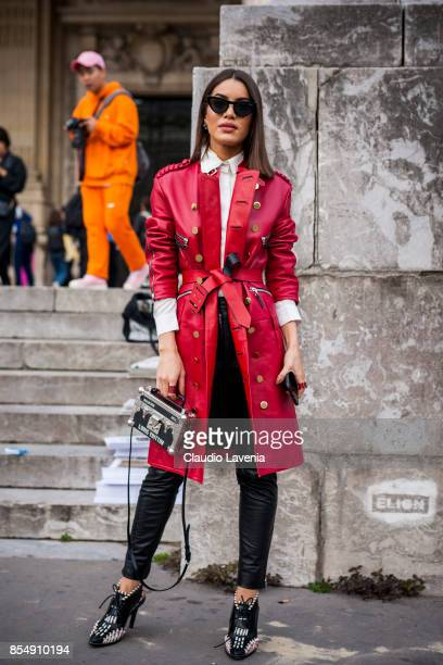 Camila Coelho wearing a red leather trench black leather pants and Louis Vuitton bag is seen before the Maison Margiela show at the Grand Palais...