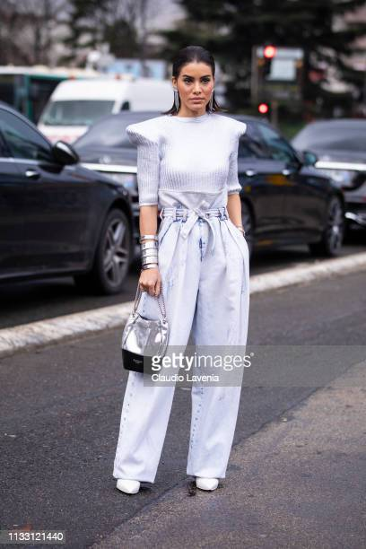 Camila Coelho, wearing a silver top, silver pants, white heels and silver and black bag, is seen outside Balmain on Day 5 Paris Fashion Week...