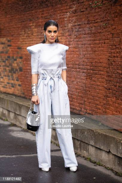 Camila Coelho wearing a silver top silver pants white heels and silver and black bag is seen outside Balmain on Day 5 Paris Fashion Week...