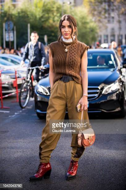 Camila Coelho wearing a sleeveless brown sweater tan pants red boots and Chloe bag is seen after the Chloe show on September 27 2018 in Paris France