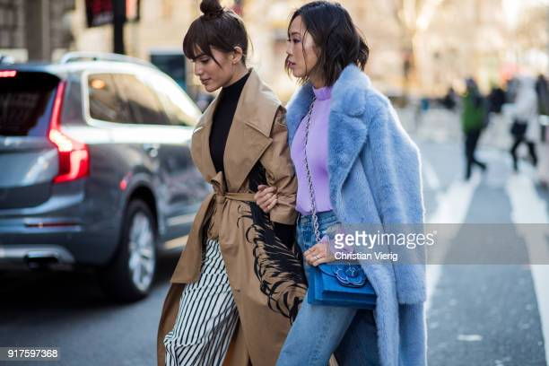 Camila Coelho wearing brown trench coat striped pants and Aimee Song seen outside Oscar de la Renta on February 12 2018 in New York City