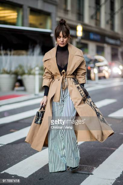 Camila Coelho wearing brown trench coat striped pants seen outside Oscar de la Renta on February 12 2018 in New York City