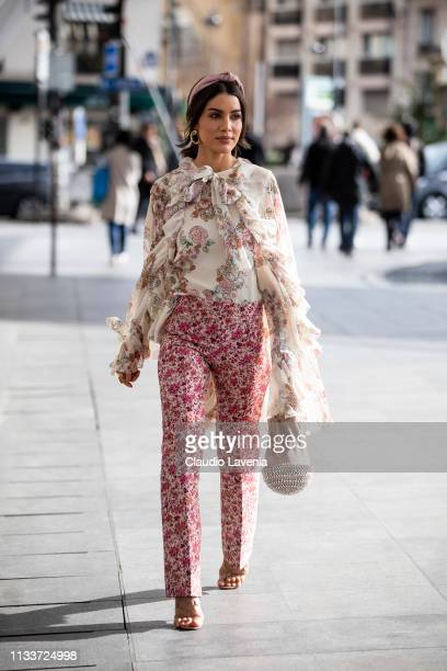 Camila Coelho wearing floral print blouse flora print trousers pink bag and nude sandals is seen outside Giambattista Valli on Day 8 Paris Fashion...