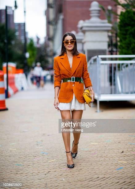 Camila Coelho wearing orange blazer is seen outside Tory Burch during New York Fashion Week Spring/Summer 2019 on September 7 2018 in New York City