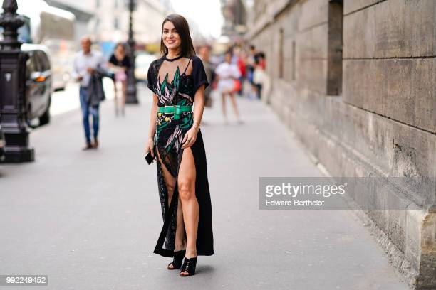 Camila Coelho wears a black lace mesh dress with embroidered flowers a green belt outside Elie Saab during Paris Fashion Week Haute Couture Fall...