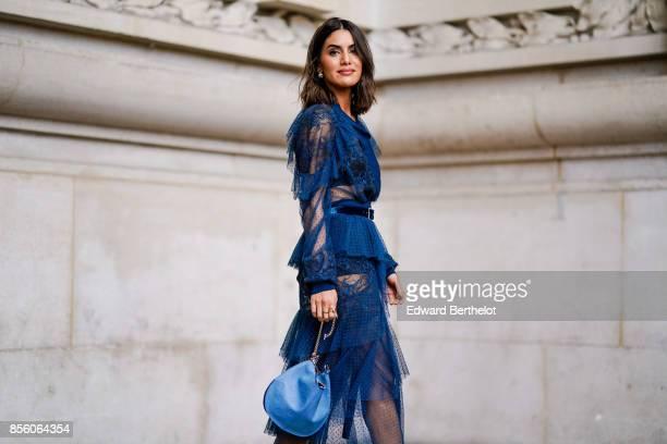 Camila Coelho wears a blue mesh lace dress, a blue bag, outside Elie Saab, during Paris Fashion Week Womenswear Spring/Summer 2018, on September 30,...