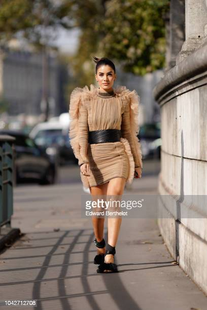 Camila Coelho wears a brown lace dress with ruffles a large belt outside Balmain during Paris Fashion Week Womenswear Spring/Summer 2019 on September...
