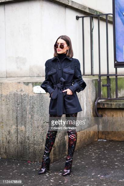 Camila Coelho wears a dark jacket floral print pants shoes during Paris Fashion Week Haute Couture Spring Summer 2020 on January 23 2019 in Paris...