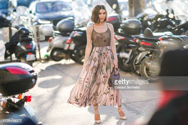 Camila Coelho wears a floral print pleated dress a Dior Saddle bag outside Dior during Paris Fashion Week Haute Couture Spring Summer 2020 on January...