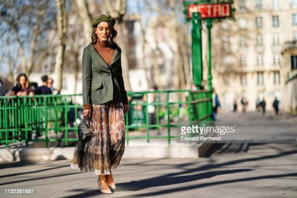 Camila Coelho wears a green beret hat a green blazer jacket a brown wool turtleneck pullover a Dior monogram Saddle bag a colored pleated skirt Dior...