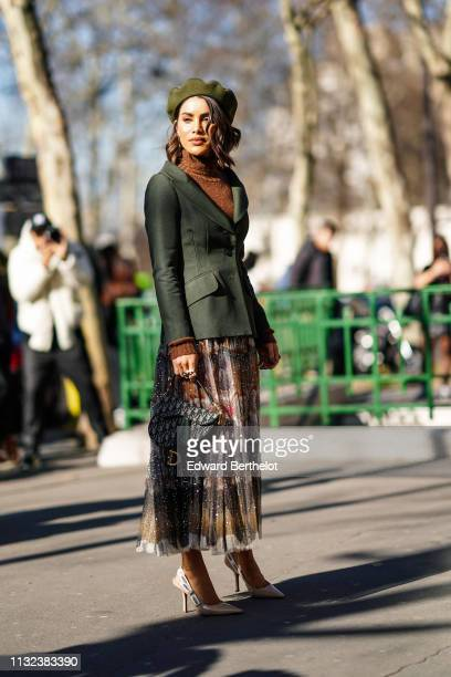Camila Coelho wears a green beret hat, a green blazer jacket, a brown wool turtleneck pullover, a Dior monogram Saddle bag, a colored pleated skirt,...