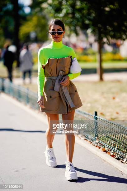 Camila Coelho wears a green yellow turtleneck top a brown dress white sneakers shoes outside Margiela during Paris Fashion Week Womenswear...