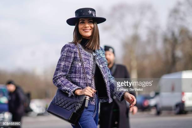 Camila Coelho wears a hat a tweed jacket blue jeans a Chanel black bag outside Chanel during Paris Fashion Week Womenswear Fall/Winter 2018/2019 on...