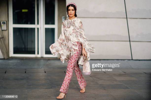 Camila Coelho wears a headband a ruffled lace floral print top pink floral print pants a bag outside Giambattista Valli during Paris Fashion Week...