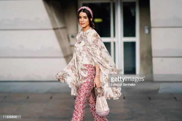 Camila Coelho wears a headband a ruffled lace floral print top pink floral print pants a bag outside Giambattista Valli during Paris Fashion Week...
