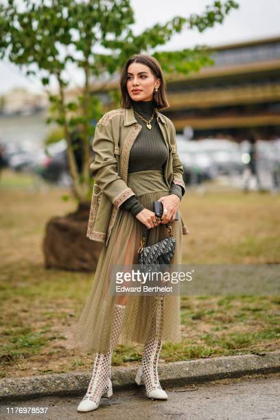 Camila Coelho wears a khaki green jacket, a golden necklace, green turtleneck wool pullover, a Dior monogram Saddle bag, white mesh boots, outside...